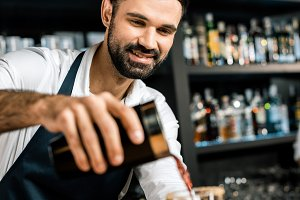 smiling barman pouring cocktail from