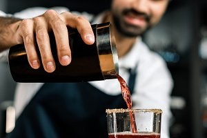 barman pouring cocktail from shaker