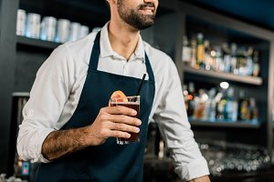 Bartender standing in apron with coc