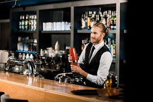 Handsome barman mixing drink in shak