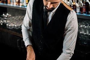 Bartender standing in bar and cuttin