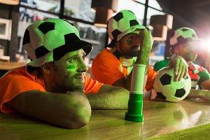Football fans sitting in hats, watch