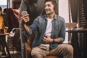 two smiling men using smartphone wit