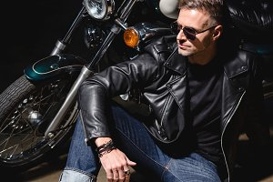 handsome biker in sunglasses sitting