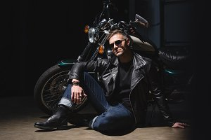 handsome biker in sunglasses standin