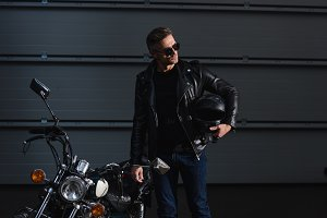 handsome biker in sunglasses holding