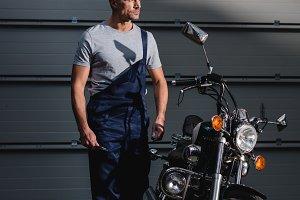 adult mechanic in overalls standing