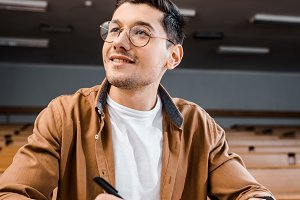 smiling male student in glasses sitt