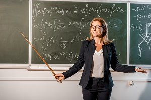 smiling female teacher with wooden p