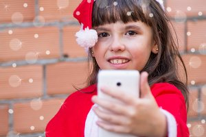 girl dressed as santa claus making a