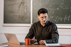 pensive male teacher in glasses sitt