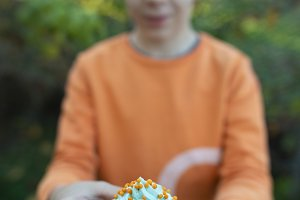 Boy holding blue color muffin