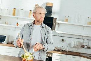 adult man cooking vegetable salad an