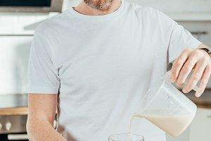 adult man pouring banana protein sha