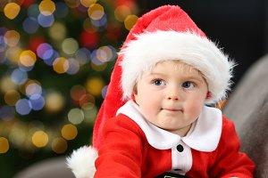 Pensive baby wearing santa costume