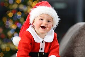 Cheerful baby dressed as santa claus
