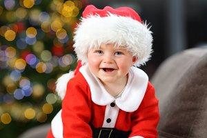Baby wearing santa disguise looking