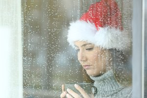 Sad woman in christmas in rainy day