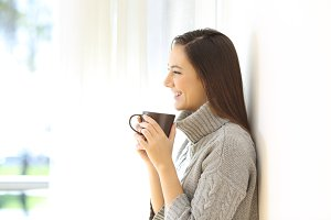Profile of a woman holding a coffee