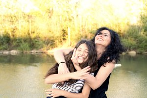 Teen girl and her mother are hugging