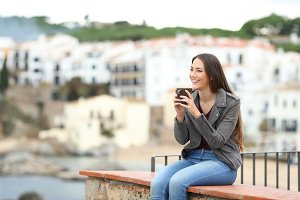Happy woman on a ledge drinking