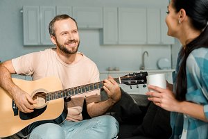 smiling husband playing acoustic gui