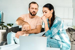 couple sitting on couch, using lapto