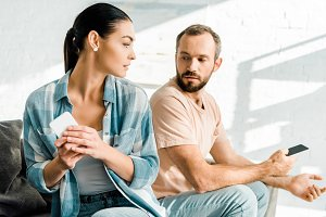 dissatisfied couple sitting on couch