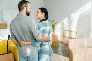 happy couple embracing while packing