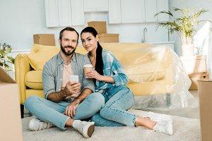 couple drinking coffee, using smartp