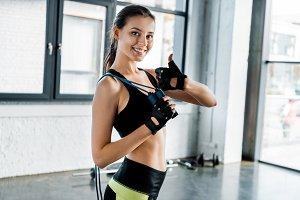 smiling sportswoman holding skipping