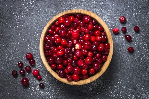 Cranberry in wooden bowl on black
