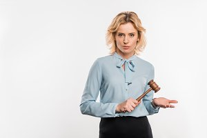 serious female judge holding wooden