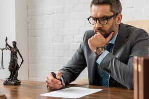 focused male lawyer in eyeglasses wo