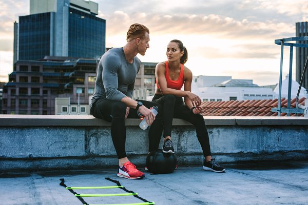 Fitness couple sitting on rooftop
