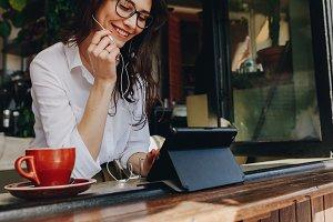 Freelancer at cafe making a call