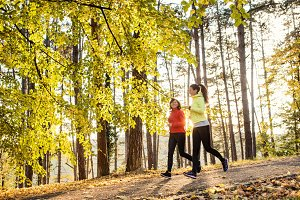 Two female runners jogging outdoors