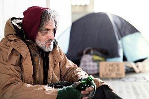 A homeless beggar man sitting