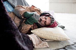 Homeless beggar man lying on the