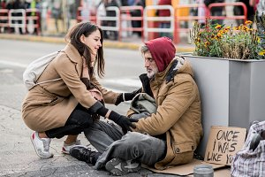Young woman giving money to homeless