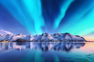 Northern lights and snowy rocks