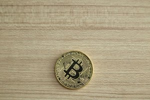 Golden Bitcoin coin on wood backgrou