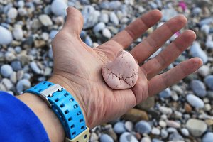 Pink stone in left hand on the beach