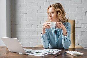 smiling businesswoman holding cup of
