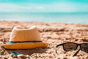 Sunglass and cap on sand against tur