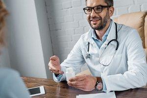smiling doctor showing jar of medici