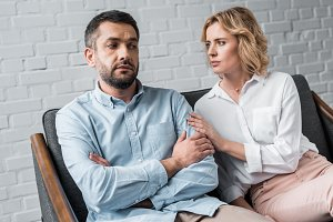 woman talking to depressed husband w