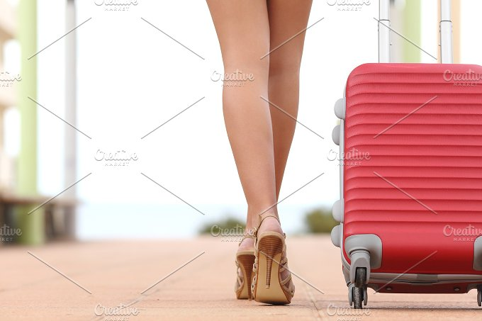 Back view of a traveler woman legs walking with a suitcase.jpg - Holidays