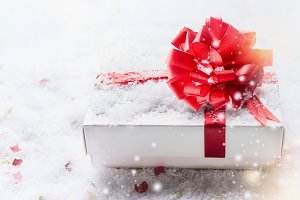 Gift box with red bow on snow