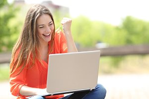 Euphoric woman searching job with a laptop in a park.jpg